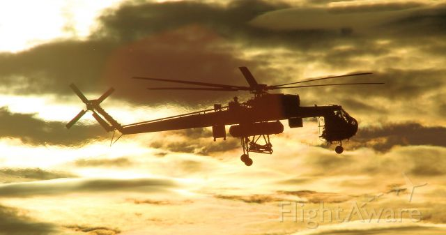 — — - Erickson Sky Crane landing as the sun is setting in the background.