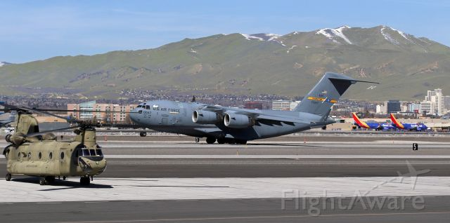 Boeing Globemaster III (97-0047) - United States Air Force C-17A Globemaster III (970047)<br />315th AW (Airlift Wing), United States Air Force Reserve<br />(Integrated with) 437th AW, United States Air Force Active<br />Air Mobility Command<br />Joint Base Charleston, South Carolina<br /><br />United States Army CH-47F Chinook (10-08855)<br /><br />A US Army Chinook, rotors turning, waits until a USAF C-17 Globemaster takes off behind it on Runway 16L before beginning to taxi to Runway 25 to make its own departure from RNO.