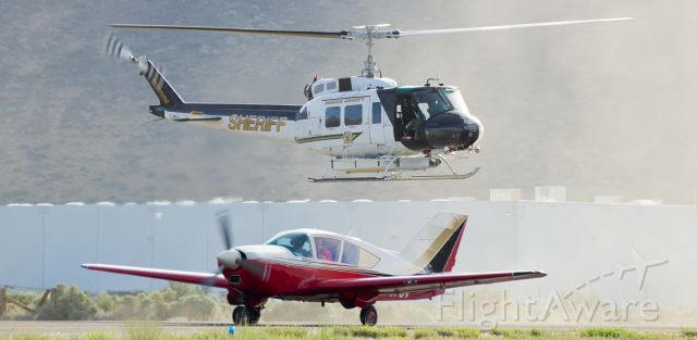 """N911NV — - It may appear that """"RAVEN One,"""" the Washoe County Sheriff Departments Bell HH-1H Iroquois helicopter, is making a traffic stop on a Bellanca, but in reality the WCSDs R(egional) AV(iation) EN(forcement) helicopter is just kicking up a bit of dirt as it waits for the just-landed Bellanca to taxi to the Carson City Airport ramp.  Both aircraft were arriving to participate in the annual Carson City Airport Open House."""