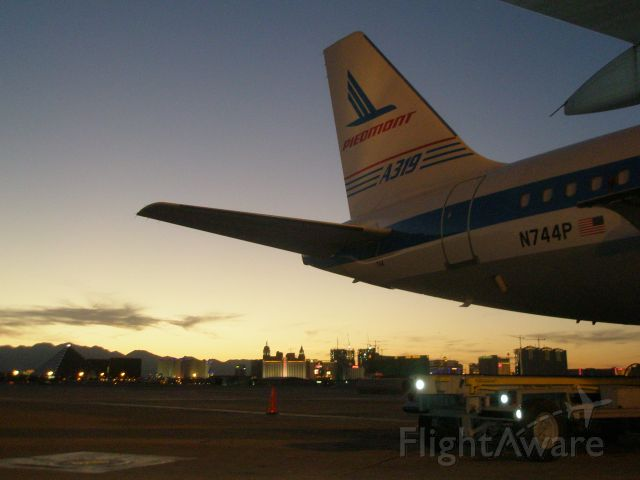 Airbus A319 (N744P) - Piedmont throw-back plane, on the ramp in Las Vegas during a beautiful sunset