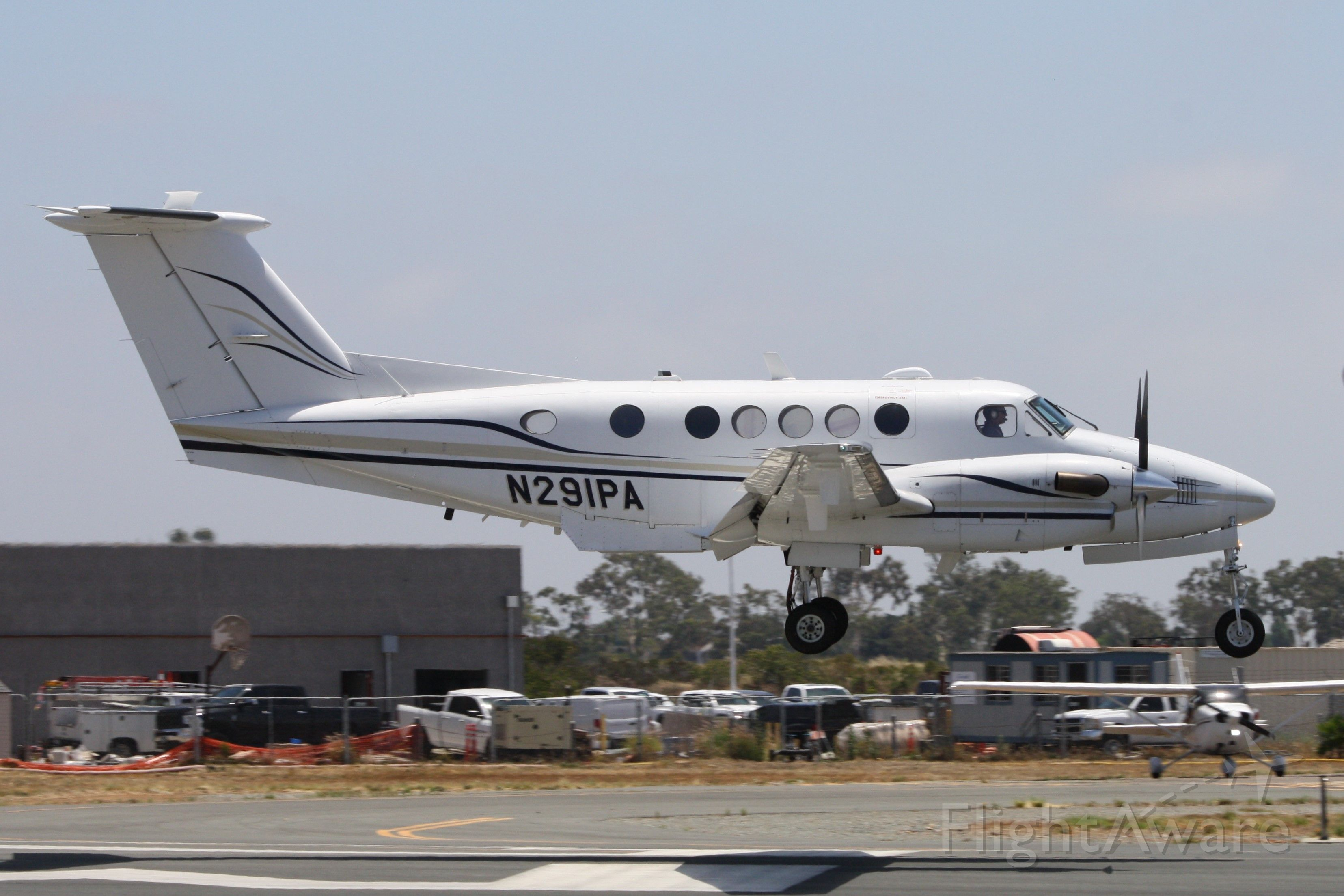 Beechcraft Super King Air 200 (N291PA) - A King Air from Northrop Grumman with special equipment. Landing at Mongtomery Gibbs Executive Airport in San Diego, July 17 2019. Taken from the 94th Aero Squadron restaurant adjacent to runway 23.