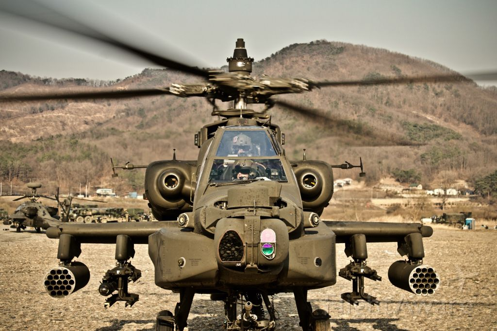— — - A AH-64D executing gunnery operations prepares to take off from an improved landing site in Korea.