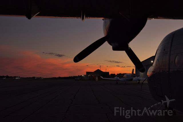 NURTANIO Aviocar — - Sunset from under the wing of a Casa C-212 towards the FBO building.