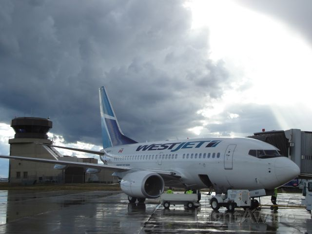 BOEING 737-600 (C-GWSK) - WestJet Boeing 737-600 at the loading bridge at the Fort McMurray Alberta Airport on July 25th, 2007. The storm brewing to the west in the picture developed into a hailstorm with golfball sized stones that caused significant damage to homes just west of the airport.
