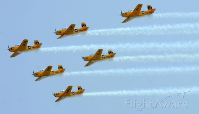 — — - The entire LimaLima flight team flies by in formation as they setup for their 6-ship loop.