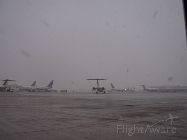 McDonnell Douglas MD-90 — - Typical snow storm; deice in progress in background.