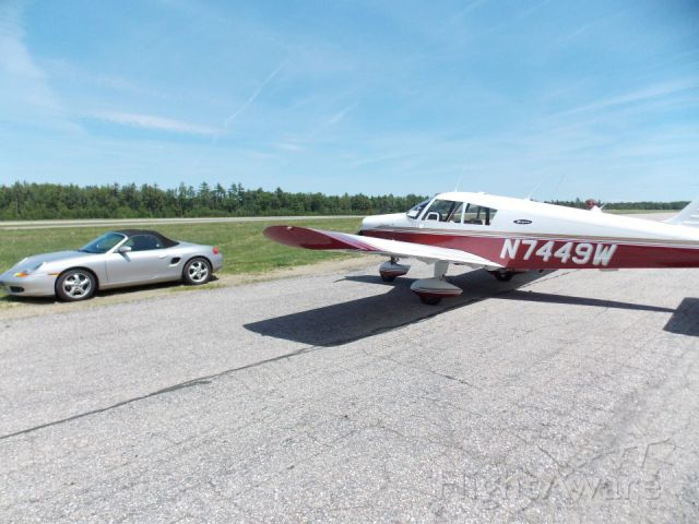 Piper Cherokee (N7449W) - outside of the hanger parked next to the little Porsche