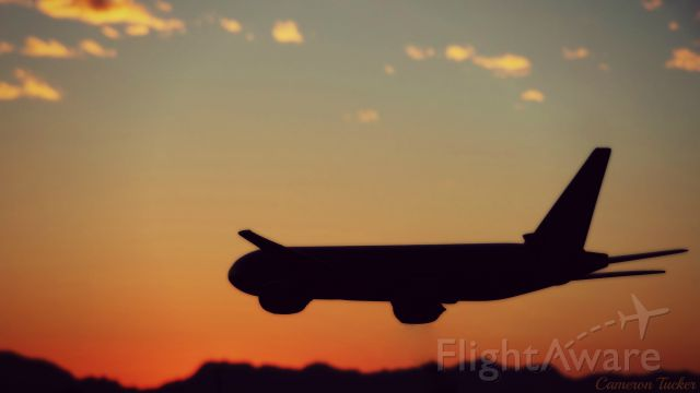 Boeing 777 (N777UA) - Had to share this picture! This is my United 777-200 model airplane as the sun was setting over the mountains west of Tucson. I photo-shopped the stand out of the picture.