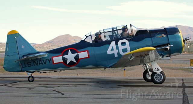 """North American T-6 Texan (N2983) - Displaying two different race numbers (Race 48 on the fuselage but Race 49 on the landing gear well cover), """"Playtime,"""" a North American T-6G Texan (N2983), is captured as it taxies past me heading toward Runway 26 for takeoff."""
