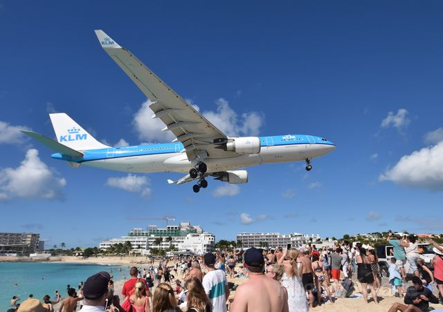 """Airbus A330-300 (PH-AON) - A-330 over Maho Beach, St Maarten. Since the hurricane the beach and beach bar has been restored with continuing work to reopen the hotels and other facilities nearby. The old """"blast area"""" on the fence is now off limits."""