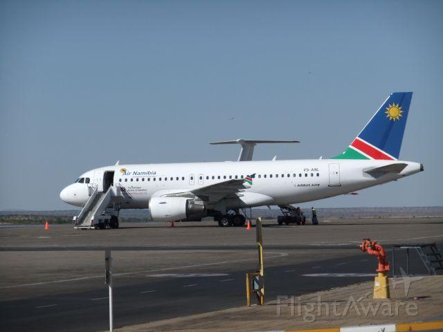 V5-ANL — - Eine der 4 neuen A319-100 der Air Namibia, ebenfalls am Nachmittag des 09.10.2011 auf dem Vorfeld WDH fotografiert. Im Hintergrund ist das riesige Seitenleitwerk der IL-76M UR-17618 der Air Almaty zu sehen, die am 07.10.2011 hier reinkam.