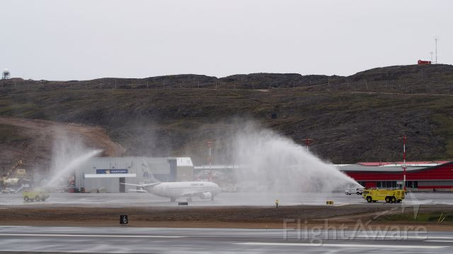 BOEING 737-400 (C-FFNM) - C-FFNM, First Air Boeing 737-400, the first southern passenger flight arrives at Iqaluits new International airport. Receiving a water cannon salute.