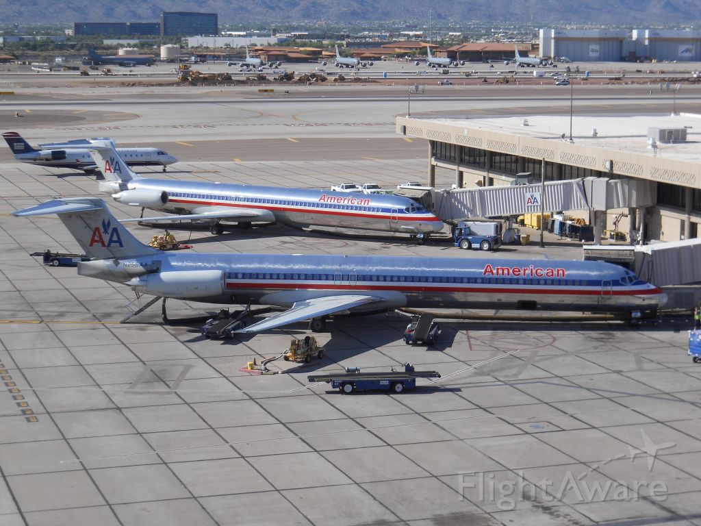 McDonnell Douglas MD-82 (N258AA) - Two American Airlines MD-80s at the gate at Phoenix Sky Harbor Airport, with a Mesa Airlines CRJ-200 taxiing behind.
