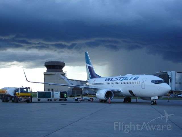 Boeing 737-700 — - WestJet Boeing 737-700 on the ramp at Fort McMurray Airport, Alberta, Canada with a storm brewing to the west.