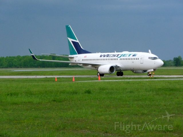 Boeing 737-700 (C-FWBW) - Taxing to CYXU/YXU terminal,Early evening after a thunderstorm had just passed by.