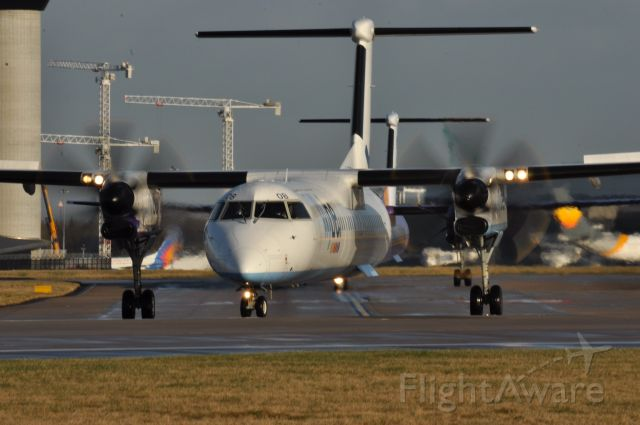 G-ECOB — - Two Dash 8s heading to runway 23L at Manchester . Southside .