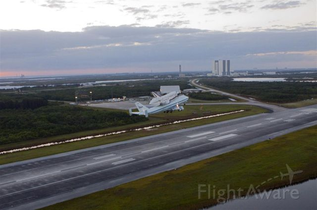 Boeing Shuttle Carrier (NASA905) - Climbing out of the SLF (KTTS) with the VAB in the background.