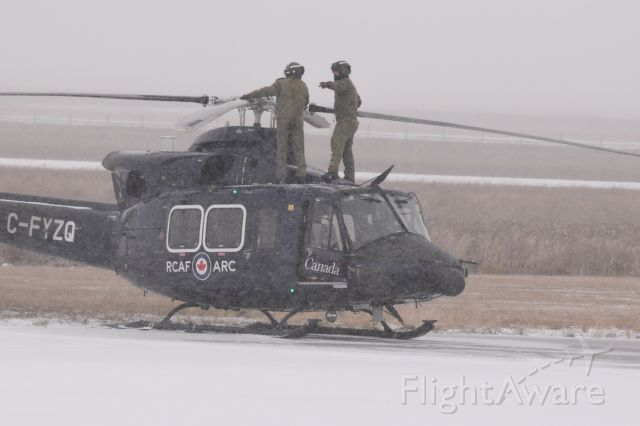 Bell 412 (C-FYZQ) - RCAF crew checking the rotors on this Bell 412 prior to a very snowy departure from Yorkton. It created the biggest snow wash ive ever had. Was totally cool (ah cold)!!