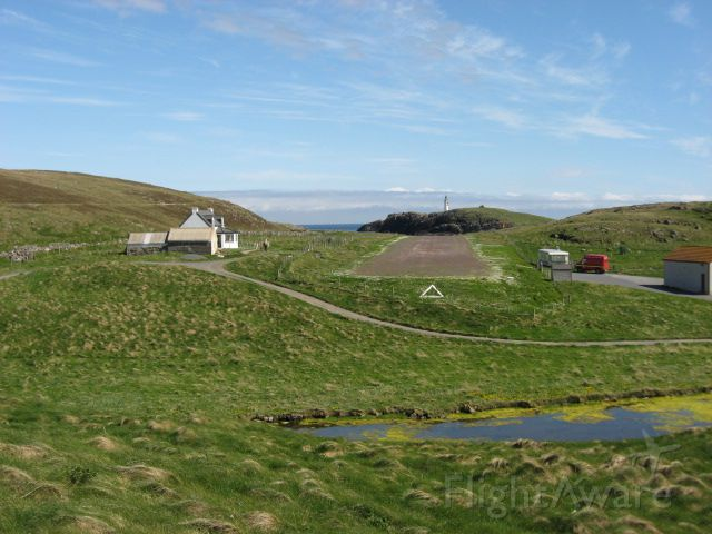 — — - AS view down the runway at Out Skerries Shetland UK. 1246ft gravel runway. The house on the left is available for rent