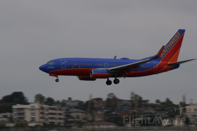 Boeing 737-700 (N448WN) - The Spirit of Kitty Hawk plane lands at San Diego International Airport 3.25.14 arriving from Denver.  Operating as Southwest 3872. Taken with a Sony Nex 6 with a 210mm lens.