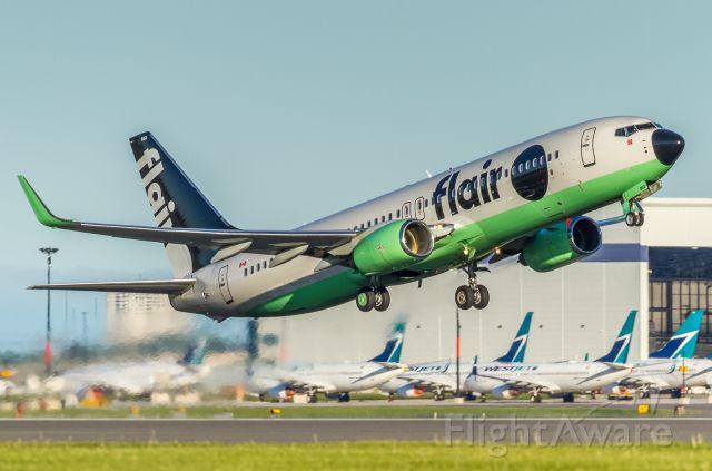 Boeing 737-800 (C-FFLC) - This Flair 738 blasting off runway 06L. Some parked Westjet birds in the background!