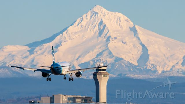 Airbus A320 (N836VA) - N836VA coming into KPDX with a clear Mt. Hood as a lovely back drop with the tower inbetween.