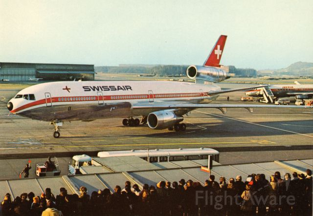 McDonnell Douglas DC-10 (HB-IHA) - This is a postcard I purchased back in the early 1970's. I did not photograph this image! It depicts a McDonnell Douglas DC-10-30 arriving with folks viewing the aircraft above the arrival gate. Also in the scene is a partial front part of the national airlines of Spain, Iberia. A commenter has noted that Iberia is a DC-8-52. <br />Cielo despejado para nuestros miembros espanoles.