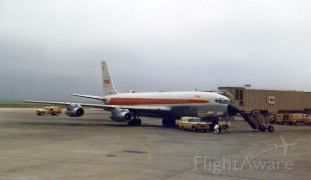"""Boeing 707-100 — - The opening earlier this year of the TWA Hotel at KJFK in New York reminded me that I had this photo so I went looking for it yesterday and finally found it at the bottom of a pile of old print pictures.<br />I'll apologize for the less-than-primo quality of this Kodacolor 620 film print, but it was taken in 1967 so it is a 52 year old photograph.  The camera used was a Kodak Bullseye.<br />It shows a TWA B707 at a gate of the Trans World Airlines Flight Center terminal at JFK. The terminal had opened five years earlier (1962) and its fabulous futuristic design resembling a bird in flight made it a """"must see"""" stop for anyone who passed thru JFK. Pictures of TWA's aircraft at the gates could be taken while standing in the central section of the main terminal area, and this photo was taken from there. The very top of the tail of a TWA B727 parked at another gate is just barely visible in the background."""