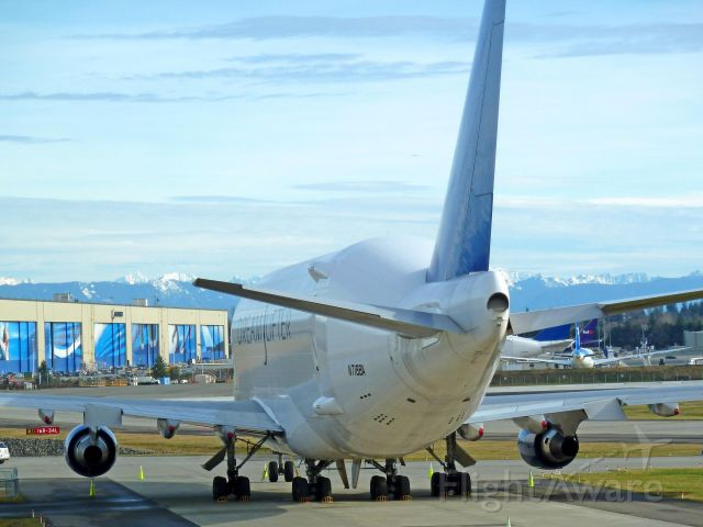 Boeing 747-400 (N718BA) - 1-28-2011 Dreamlifter 747-407 LCF, N718BA in preparation for a show parked at back of Mukilteos Future of Flight Aviation Center just west of Paine Field, Everett, Washington  ||||  Note the photo also shows the blue hangar doors of the Boeing Company Assembly plant in Everett, Washington in the background on the opposite side of the Paine Field main runway |||| Photo by Bruce McKinnon