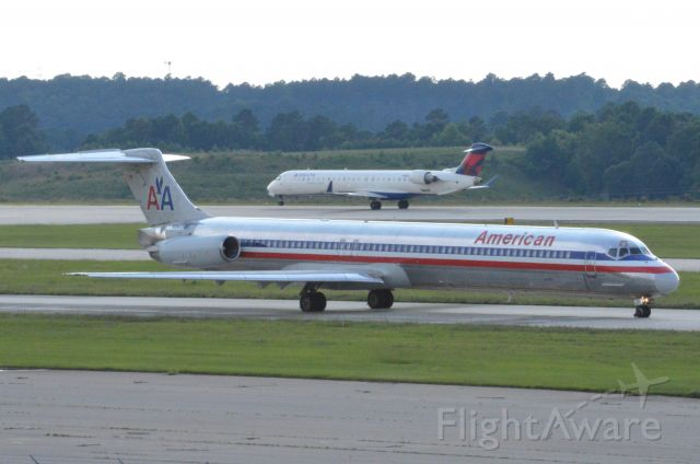 McDonnell Douglas MD-83 (N8404W) - As part of my personal AA Mad Dog Sendoff, I am posting over the next week AA MD80s I hadn't posted yet starting with this image.  Here N8404W taxies out for hist departure to Chicago O'Hare while in the background a Delta CRJ rotates on his departure to Orlando..  Photo taken June 19, 2016.