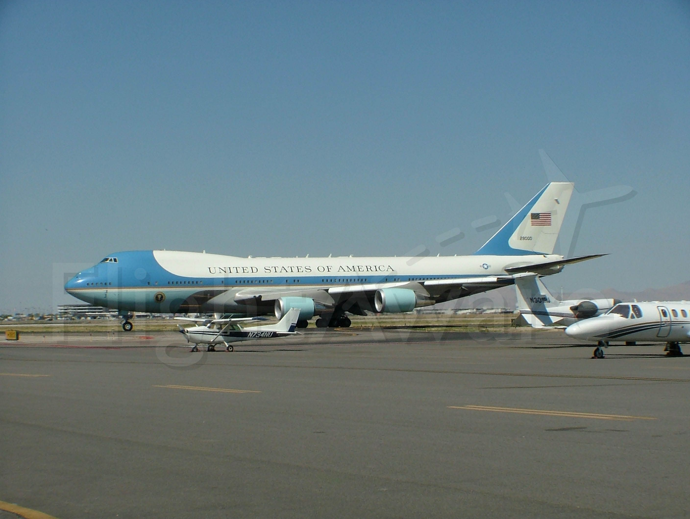 Boeing 747-200 — - Air Force One,  President G.W.Bush visit to Salt Lake City, 2006  I love how the cessna in the foreground is dwarfed by the size of AF-1 even considering it is probably 200 feet closer to the camera.