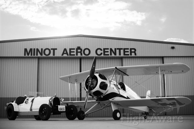 — — - büker and bugatti in front of KMOT - Minot Aero Center Hangar