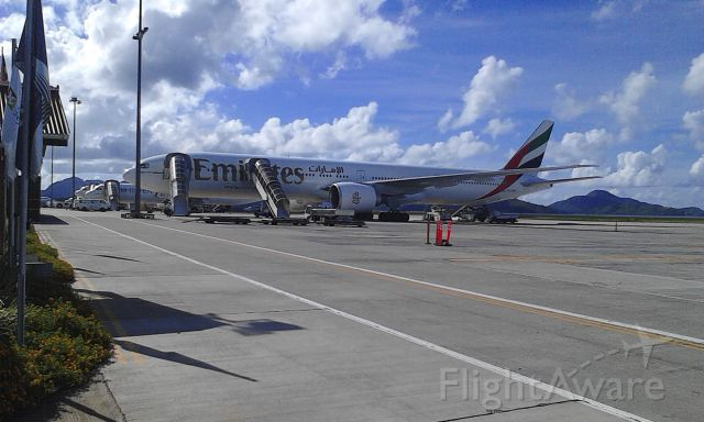 — — - Beautiful 777 sits at the airport in Seychelles. Next to a Mihin Lanka and further down an Air Seychelles.