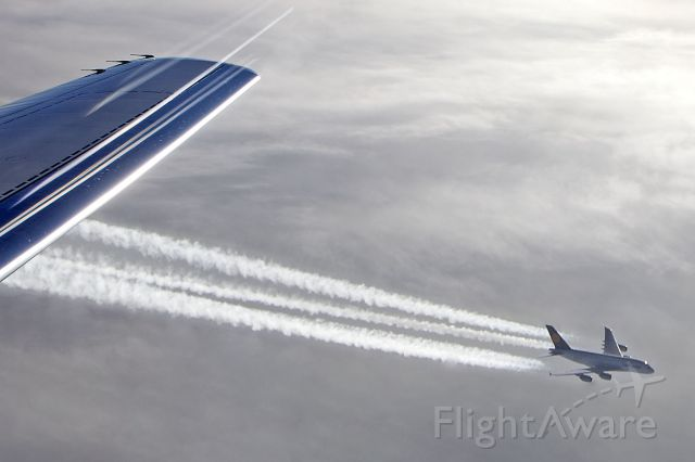 — — - A380 over Atlantic - telephoto lens appears to bring a/c closer - flare/streaks over wing as exposed into light