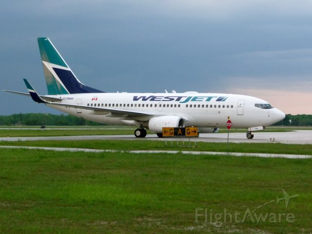 Boeing 737-700 (C-FWBW) - Taxing in to terminal after landing from westcoast,taken May 30,2009,shortly after a thunderstorm had passed by.CYXU/YXU LONDON,ONTARIO,CANADA.
