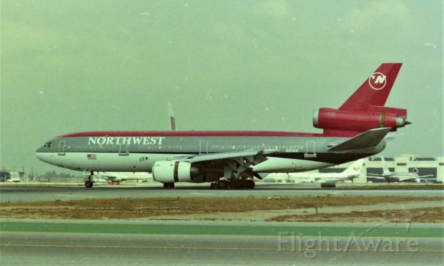 McDonnell Douglas DC-10 (N153US) - KLAX apprx March 1989 at the Imperial Terminal parking lot with a 6ft fence, this was an all day event and I may have even had to go get more film. The NWA DC10 shown here just landed on 25L and was following a UAL DC-10 to cross 25R and head to the Terminal. Looking back, I sure wish Digital cameras were available back then.....