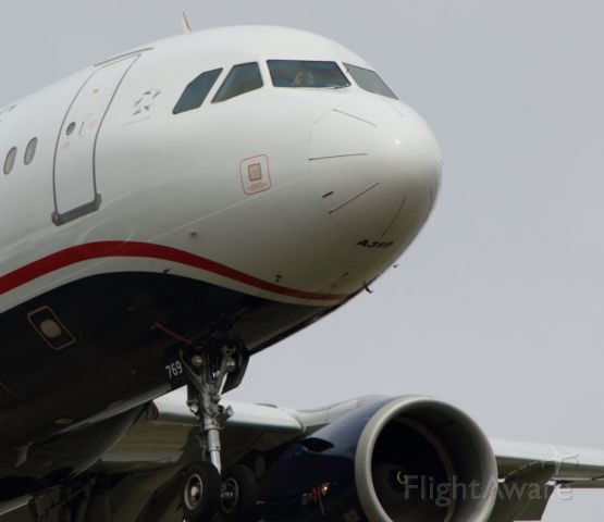 Airbus A319 (N769US) - Who's taking a picture of who? Check out the first officer. Short final runway 19
