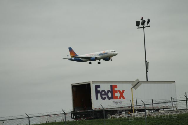 Airbus A320 (N221NV) - Allegiant Air flight 982 from KPGD arriving over the cargo ramp on runway 06.