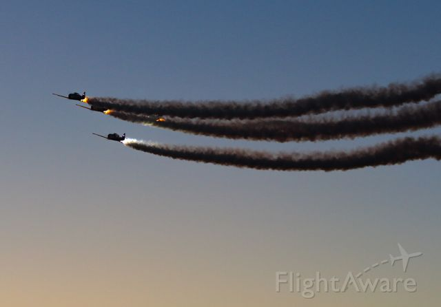 North American T-6 Texan — - Aero Shell team performing at sunset, creating an amazing image with the smoke going.