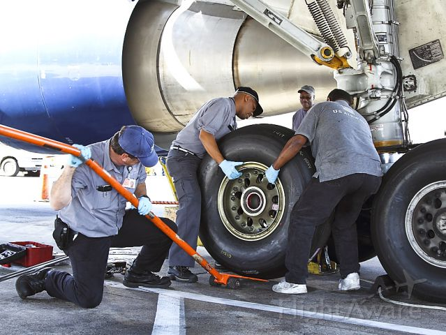BOEING 767-200 (N245AY) - A US Airways Boeing 767 gets a new #3 main tire on a quick turn around  en route to Paris. Displaying the teamwork and confidence that comes from years of training and working on the big jets, AMT