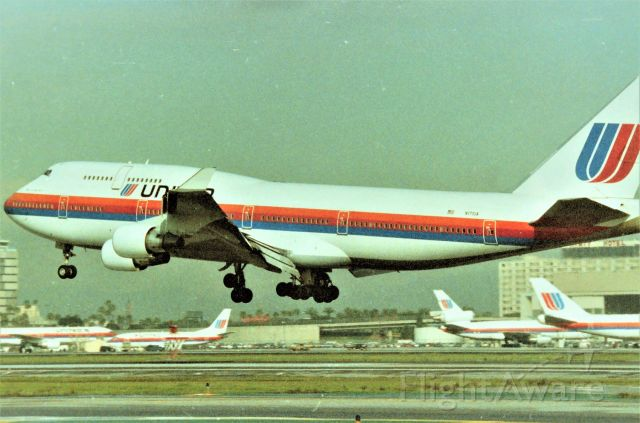 """Boeing 747-400 (N171UA) - KLAX - Sept 1989 down in LAX for the Airline Collectible show that year at the Hacienda Hotel on Sepulveda, my 60-300mm failed me or I'm a crummy photog - parked at the FedEx lot off Douglas Ave at Los Angeles, I saw this 747-400 on final for 25L..and could see it was United! I had not seen any new 747-400s for United and here was my 1st time, I had the video and my 35mm slung around my neck...."""" video or print, print of video"""" I kept asking myself as this gleaming new 747 was approaching fast - I decided prints and I'd get the next one on video. Bad part was another UAL new 747-400 never showed up while I was here....! I have a series of this jet landing here but opted for the other UALs in the background for fun. Shown here is the """"Spirit of Seattle"""" CN:24332 LN"""" 733 - one of the 1st 747-400s for United."""