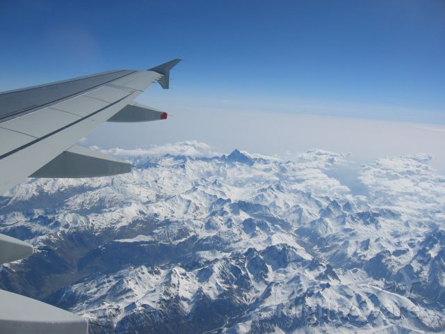 — — - View of wing over French Alps on flight from Nice to London