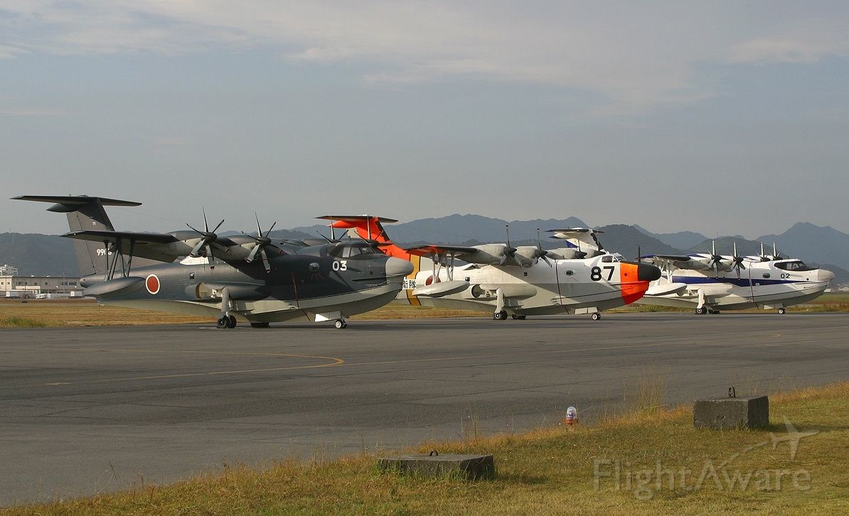 — — - Old ShinMaywa US-1A flanked by two new US-2 in different paint schemes as the sun was setting. Based at Iwakuni, Japan.