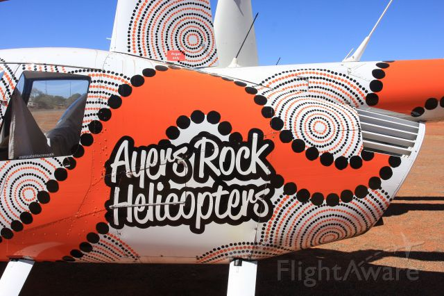 Robinson R-44 (VH-TWW) - If you are going to do heli tours of the Rock then jazz up the Robbo in Indigenous Art like this one at YARE seen recently