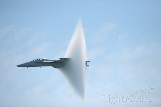 — — - A ring of water vapor is created as pilots Lt. Justin Halligan (L) and Lt. Michael Witt (R) fly their F/A-18F Super Hornet airplane within 200mph of breaking the sound barrier while performing at New York Air Show at Jones Beach in Wantagh, New York, May 23, 2009. The phenomenon is created when a plane, traveling at low altitudes over water, approaches the speed of sound and the pressure created by the forward sound waves squeezes moisture in the air to form a ball of cloud over the front of the aircraft. (Photo by Christopher Pasatieri/Reuters)