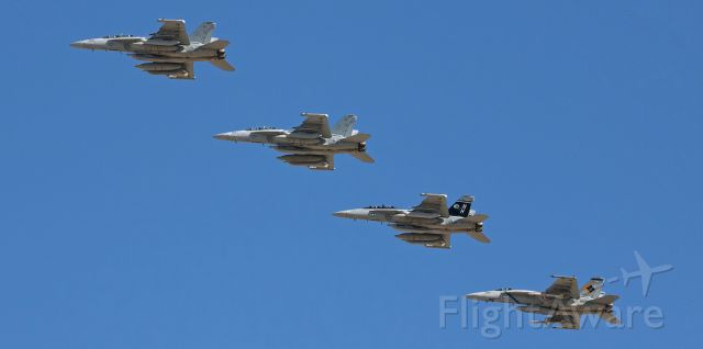 """16-8381 — - Passing over rather high up in the deep blue morning sky, a division of US Navy fighters consisting of three VAQ-142 """"Gray Wolves"""" EA-18G Growlers and a VFA-146 """"Blue Diamonds"""" FA-18E Super Hornet returns from a morning training exercise and is about to break the echelon right formation and come around to land at NAS Fallon (KNFL).  Two of the four aircraft seen here are CAG colorbirds: the """"Gray Wolves"""" CAG Growler (168381) is the third aircraft down the diagonal and the last aircraft is 165783, the VFA-146 CAG bird."""