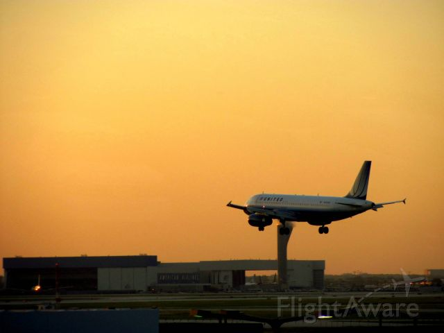 Airbus A320 (N453UA) - Taking the tram back to parking. Great sunset shot with this A320 landing on runway 27L at Chicago OHare.