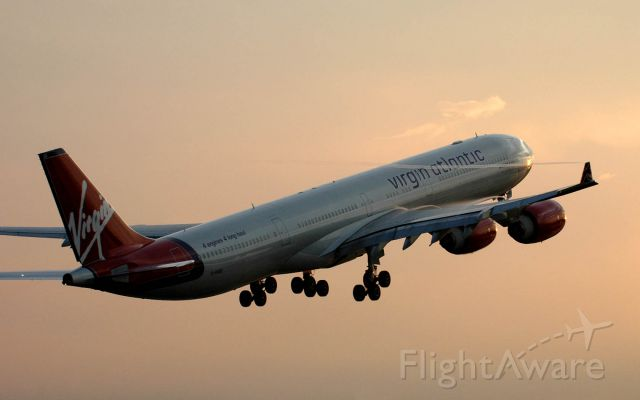 Airbus A340-600 (G-VOGE) - Taking off towards the west towards the setting sun which is reflected just under the R1 door...