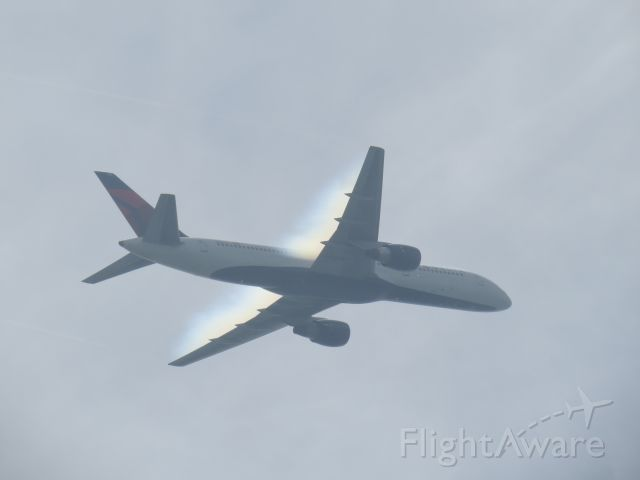 Boeing 757-200 (N654DL) - Humid air at beach provides an effect as the jet passes through.