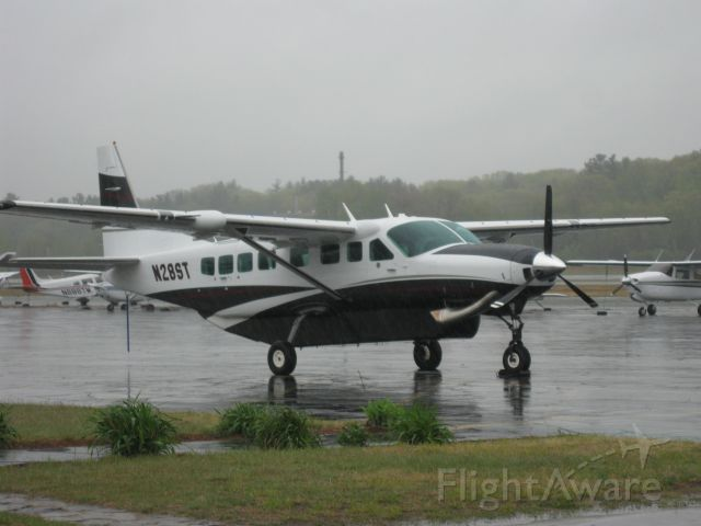 """Cessna Caravan (N28ST) - Sitting on the ramp on a very rainy, foggy day after arriving this morning from Westminster, MD (KDMW). Oxford Hill LLC sold their Piper Malibu Matrix (N6087V) and bought this nice 2010 Caravan. If you view the image in """"full"""" mode you can see the rain pouring down."""